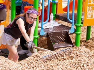 woman helps to install playground mulch